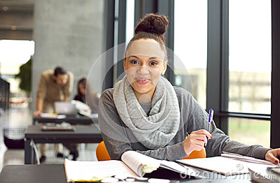 Confident female student studying in library