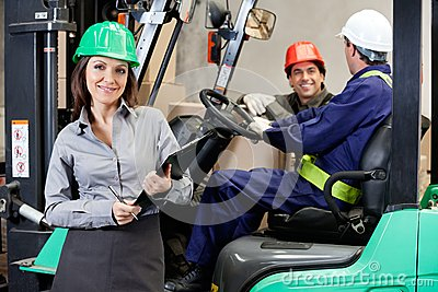 Confident Female Supervisor With Forklift Driver
