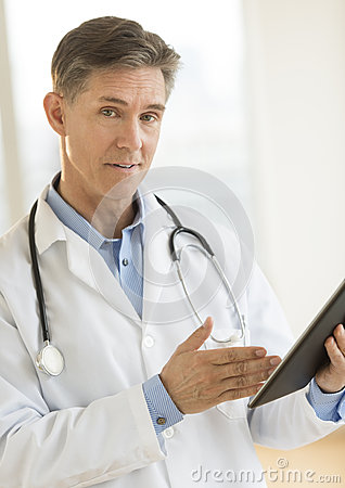 Confident Male Doctor Gesturing At Digital Tablet