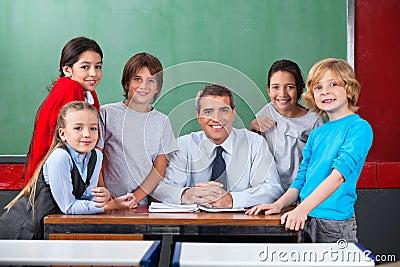 Confident Male Teacher With Schoolchildren At Desk