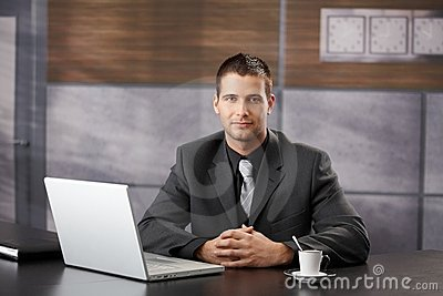 Confident manager sitting in fancy office smiling