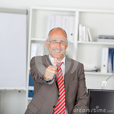 Confident Mature Businessman Gesturing Thumbs Up