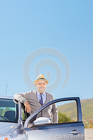 Confident mature gentleman with hat posing next to his automobil