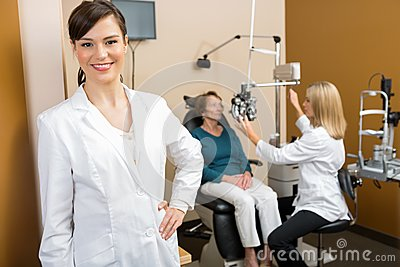 Confident Optometrist With Colleague Examining