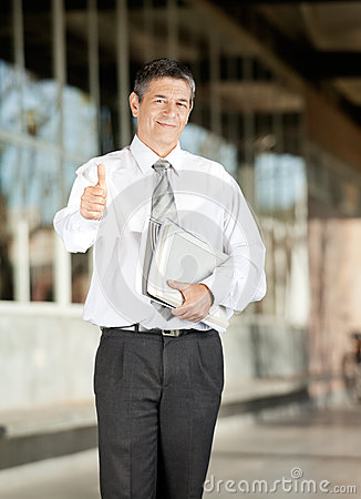Confident Teacher With Books Gesturing Thumbsup On