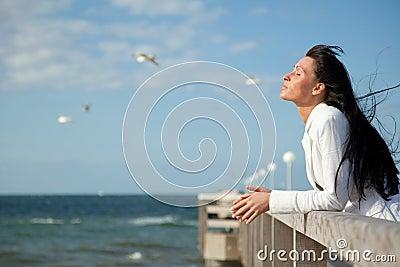 Confident wind sea coast woman