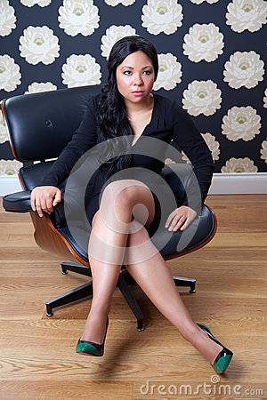 Confident woman sitting on a leather chair