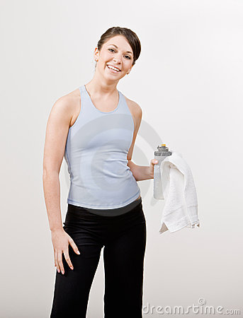 Confident woman in sportswear holding towel