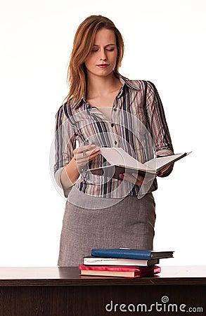 Confident woman teacher holding textbook standing