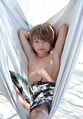 Confident young boy sitting in hammock on vacation