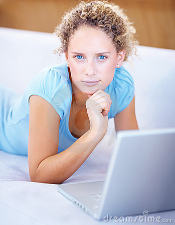 Confident young lady using laptop at home