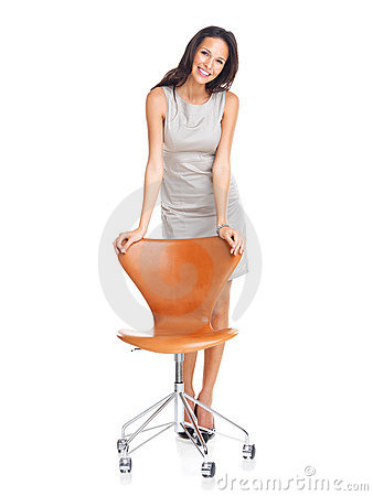 Confident young woman standing with a chair