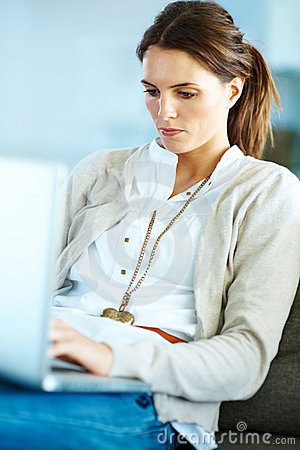 Confident young woman working on laptop