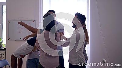 Confie a queda, equipe quedas sobre parte traseira e os colegas travam-no e aplaudem-n na terapia do grupo video estoque