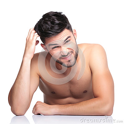 Confused beauty naked man is scratching his head