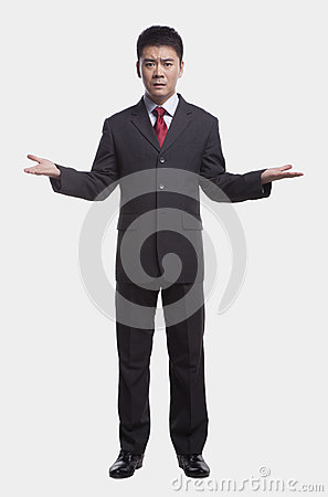 Confused Businessman with arms out to the side and palms up, full length studio shot