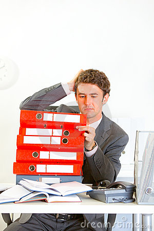 Confused businessman sitting at desk with folders