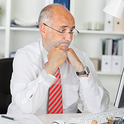 Confused Businessman Staring At Computer At Office Desk