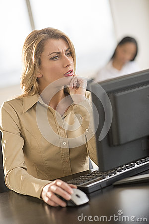 Confused Businesswoman Using Computer At Desk In Office