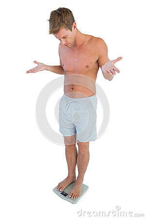 Confused man gesturing while standing on a weighing scale