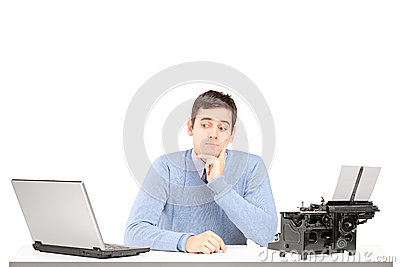 Confused man sitting on a desk with a laptop and a typing machin