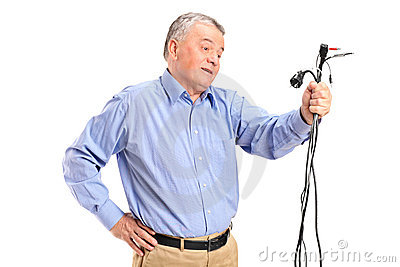 Confused senior holding electronic cables