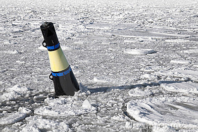 Conical black and yellow buoy on frozen sea