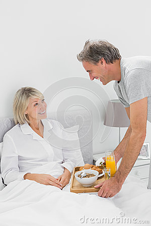 Considerate man bringing breakfast in bed to his partner