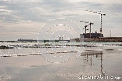 Construction cranes on beach