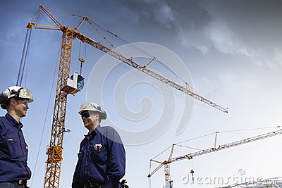 Construction cranes and building workers