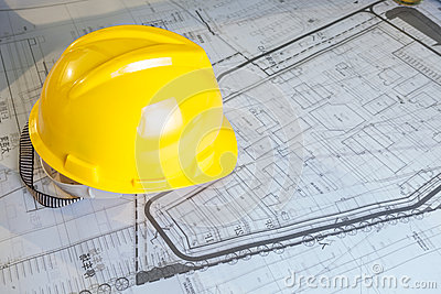 Construction plans with yellow helmet