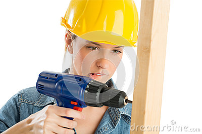 Construction Worker Biting Lip While Drilling Wooden Plank