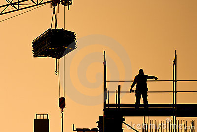 Construction worker directing crane with load