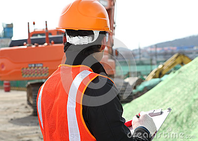 Construction worker and excavator on the background