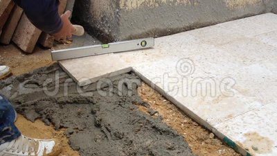 Flooring with cement outdoor. A construction worker fixing tiles of floor with cement outdoor stock video footage