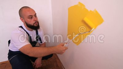 Construction worker and professional painter using paint roller brush painting of wall with yellow color. Construction worker and handyman doing finish stock footage