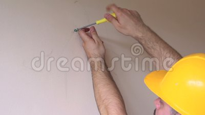 Construction worker and handyman works on renovation of apartment. Builder using yellow screwdriver screws steel screw out of wall. On construction site. House stock video