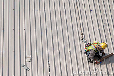 Construction worker marking roof
