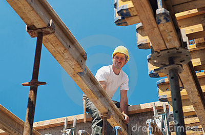 Construction worker placing formwork beams