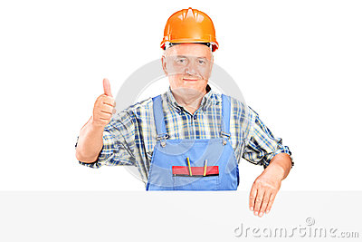 Construction worker posing behind a panel