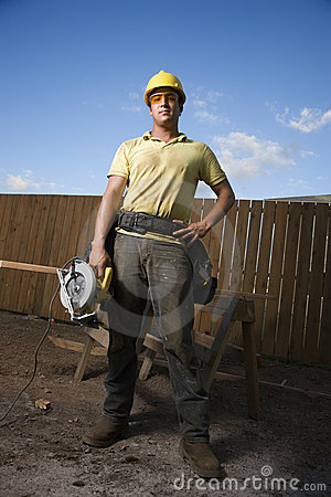Free Construction Worker Standing With Saw Royalty Free Stock Photography - 12738657