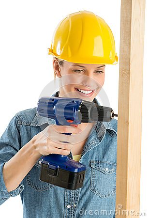 Construction Worker Using Cordless Drill On Wooden Plank