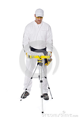 Construction worker in white coveralls level tool