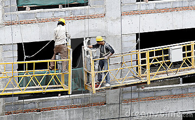 Construction workers on elevator.