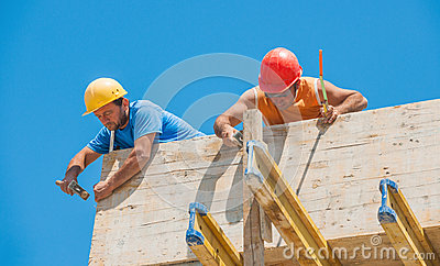 Construction workers nailing formwork in place