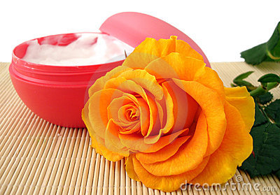 Container of cosmetic moisturizing cream with orange rose