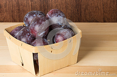 Container of prune plums on table