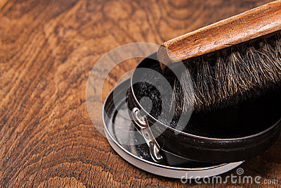 Container of shoe polish and brush on wooden