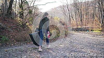 Contaminación ambiental, concepto de voluntariado Una joven con una bolsa de plástico negro y guantes en las manos se pasea almacen de video