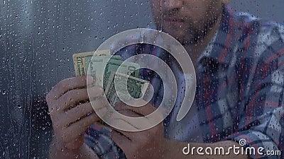 Contanti di mezza età infelici del dollaro della tenuta del maschio, bilancio insufficiente, disoccupazione video d archivio